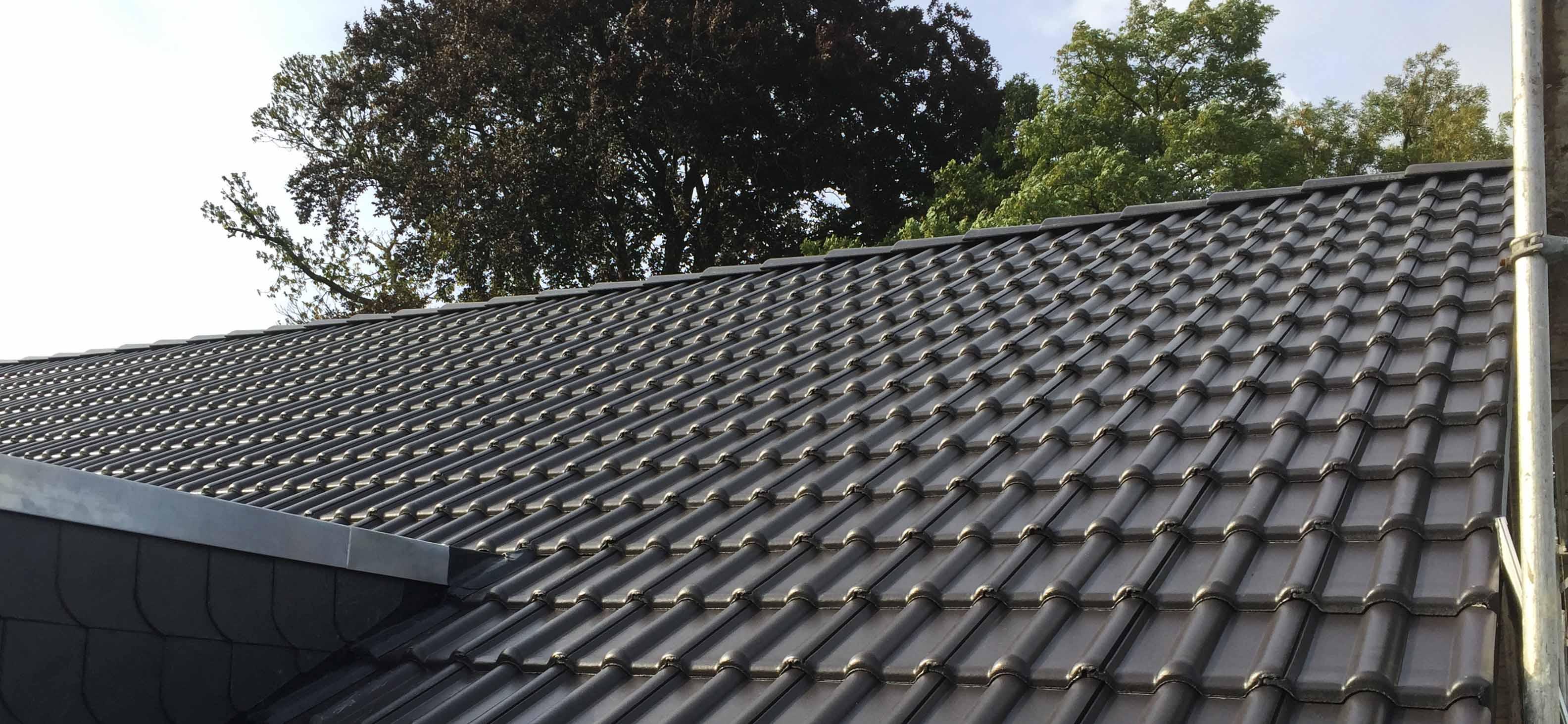 Seitenansicht eines Hausdaches mit dunkeln Ziegeln