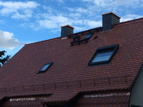 Ein Dach in der Seitenansicht mit Dachfenstern , rot braun eingedeckt